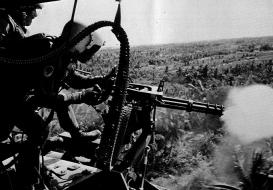 Een helikopterschutter neemt de jungle onder vuur tijdens de Vietnamoorlog